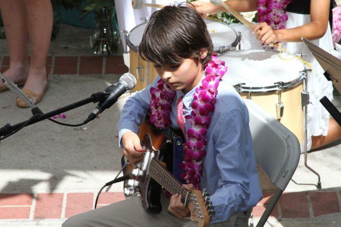 Seven Arrows Community Events 6 - Young Boy Playing Guitar with Neck Garland
